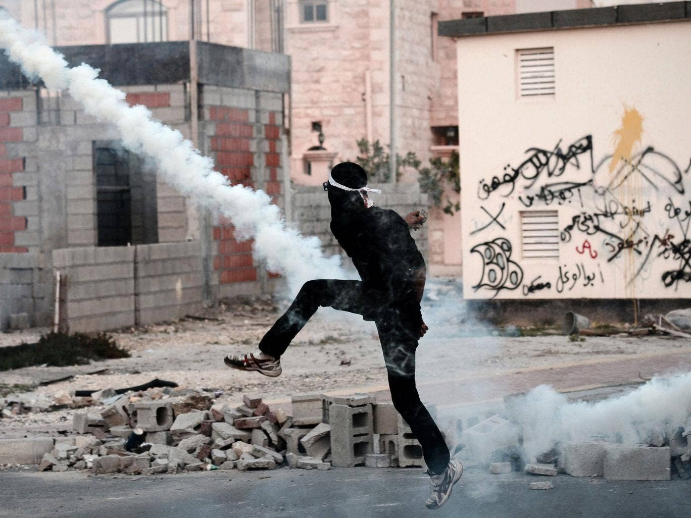 A Bahraini protester clashes with riot police following the funeral of 20-year-old prisoner Fadel Abbas Musalem in the village of Diraz on January 26, 2014