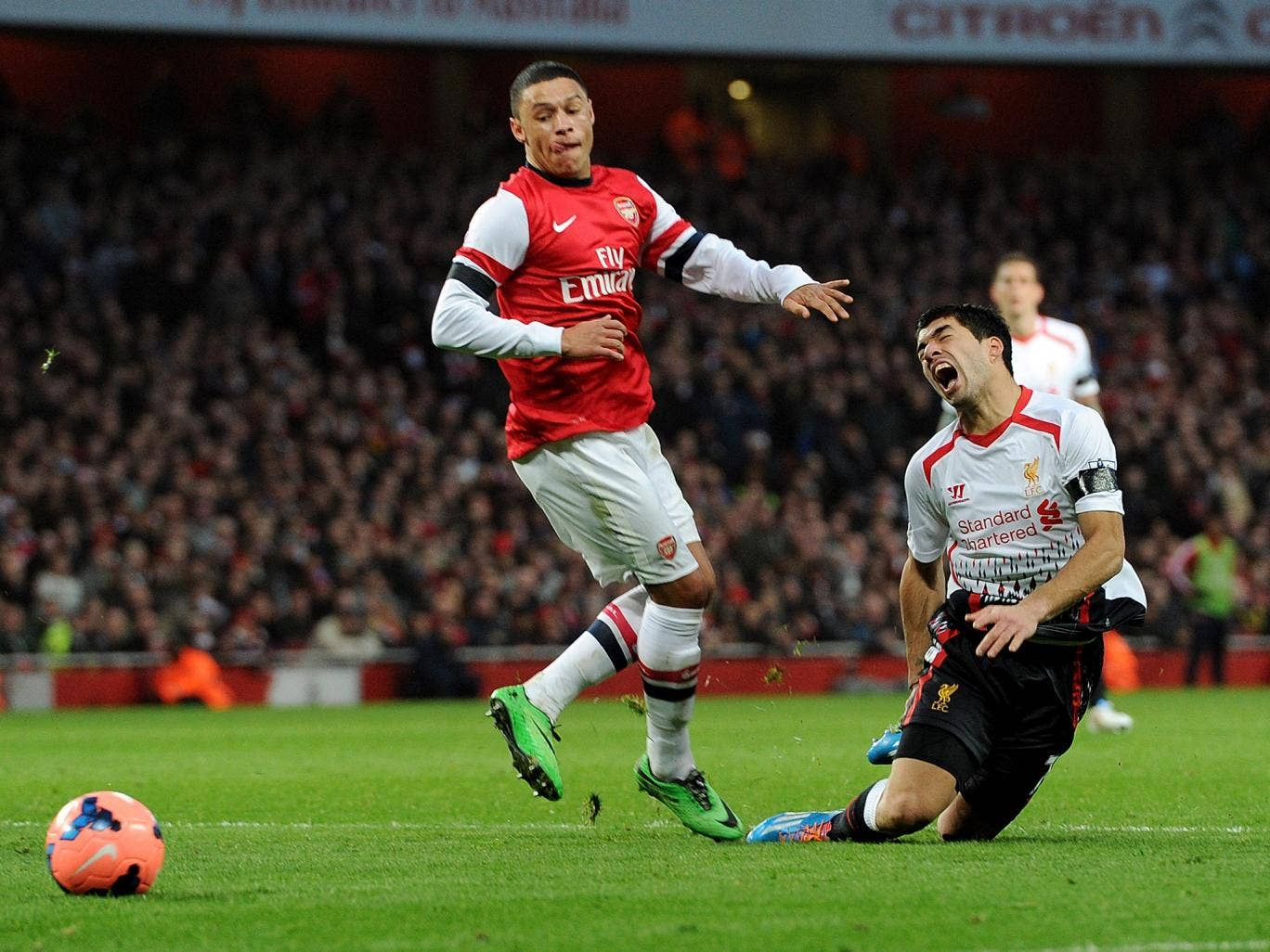 Luis Suarez of Liverpool is fouled in the box by Alex Oxlade-Chamberlain of Arsenal