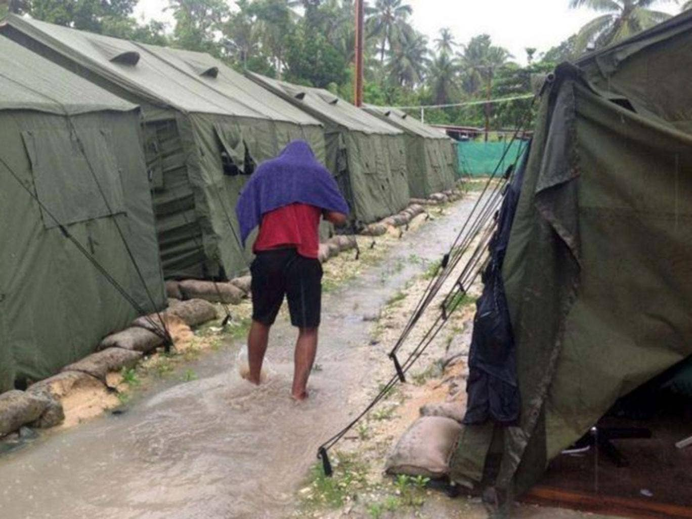 A man walks between tents at Australia's regional processing centre on Manus Island, where one inmate died in riots today