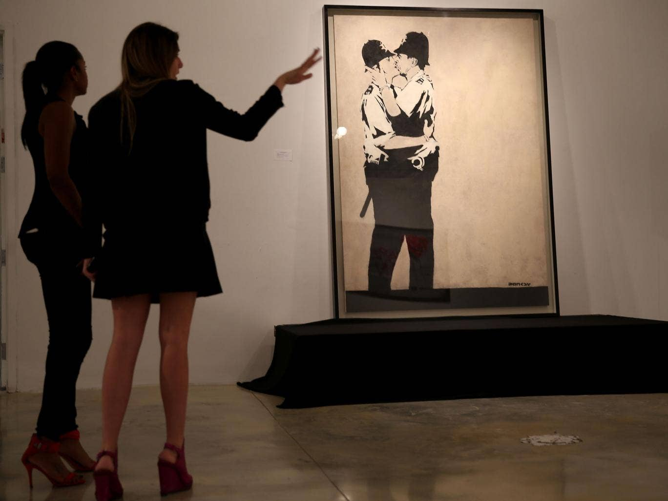 People stand in front of Banksy's 'Kissing Coppers' before it sold for $575,000 at auction in Miami