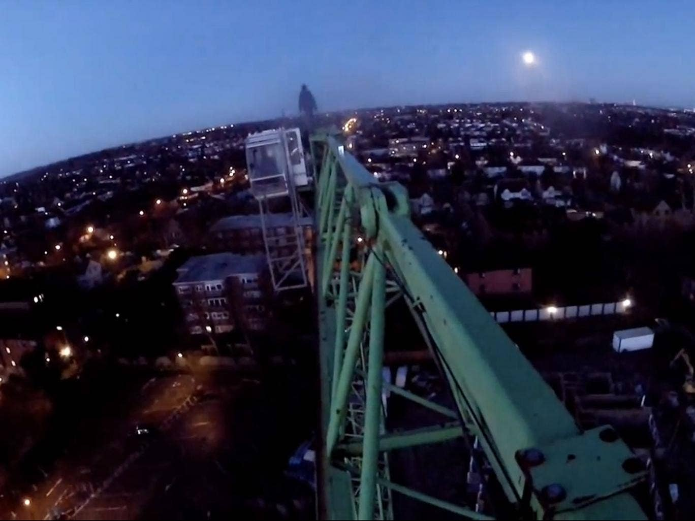 One of the climbers stands at the end of the crane, while he's filmed by others
