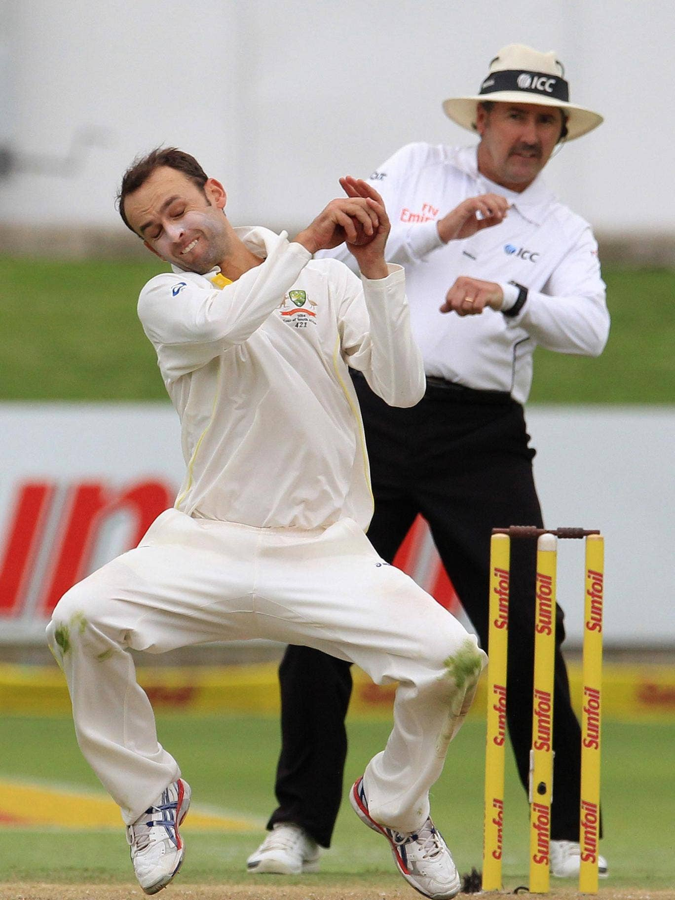 Australia spinner Nathan Lyon fields the ball from his own bowling as umpire Richard Illingworth prepares for evasive action in the background