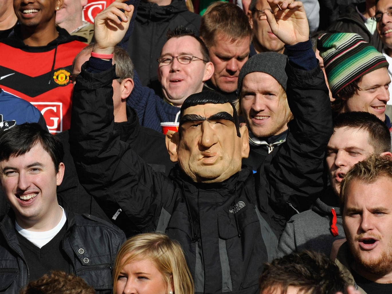 A Manchester United supporter is spotted in the crowd wearing an Eric Cantona mask