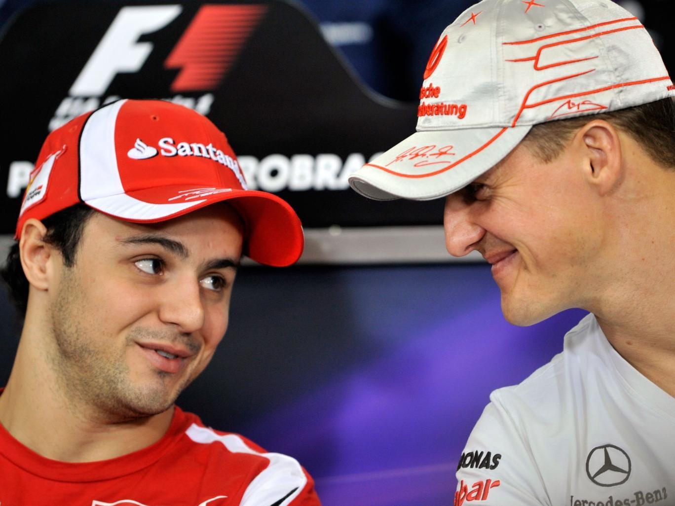 Felipe Massa and Michael Schumacher share a joke at the 2011 Brazilian Grand Prix