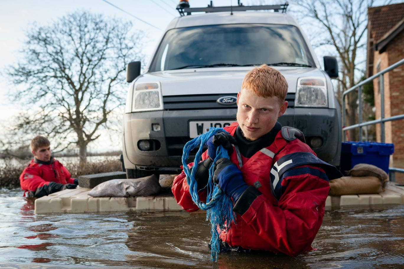 FLAG volunteers Aaron and Jay transport a trapped Environment Agency van over the flood waters on a floating pontoon