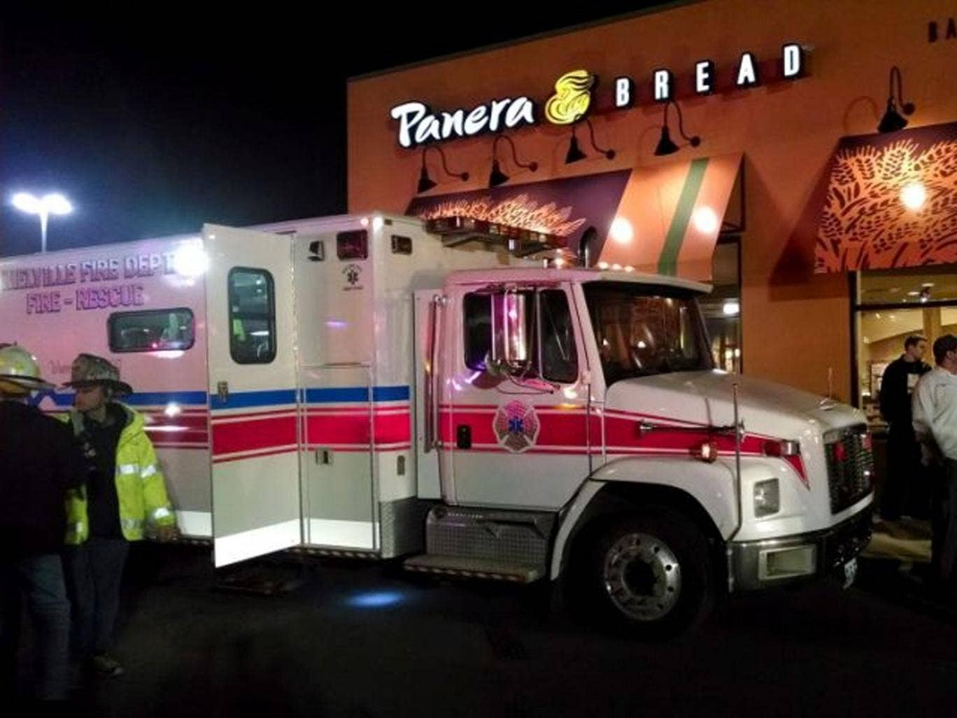 First responders stand outside Panera Bread's store at the Walt Whitman Mall in Huntington Long Island, New York late Saturday Feb. 22, 2014. Police say a 55-year-old restaurant manager has died and more than two dozen others were taken to hospitals after