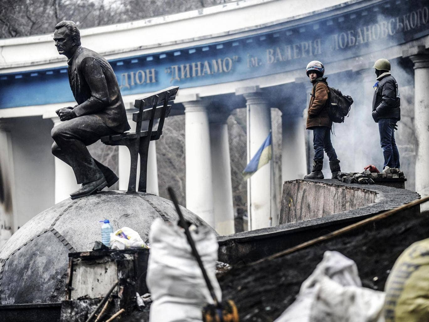 Anti-government protesters stand on a barricade at the entrance of Kiev's Independence square