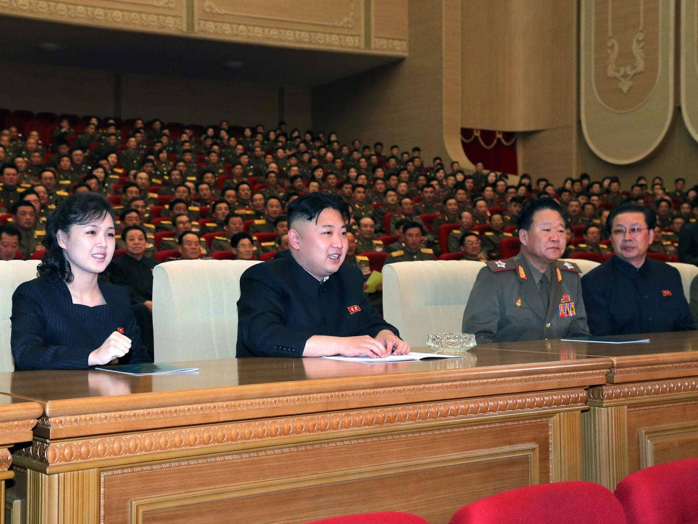 This undated picture, released by North Korea's official Korean Central News Agency (KCNA) on May 13, 2013 shows North Korean leader Kim Jong Un (C), accompanied by his wife Ri Sol Ju (L), enjoying performance given by the Song and Dance Ensemble of the K