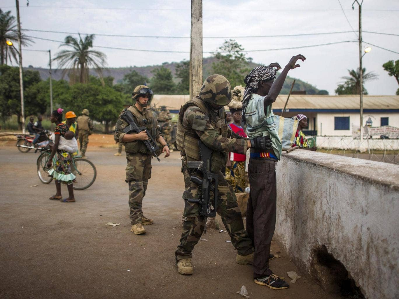 A French soldier frisks a man at a checkpoint in the PK12 district in Bangui, as Operation Sangaris continues