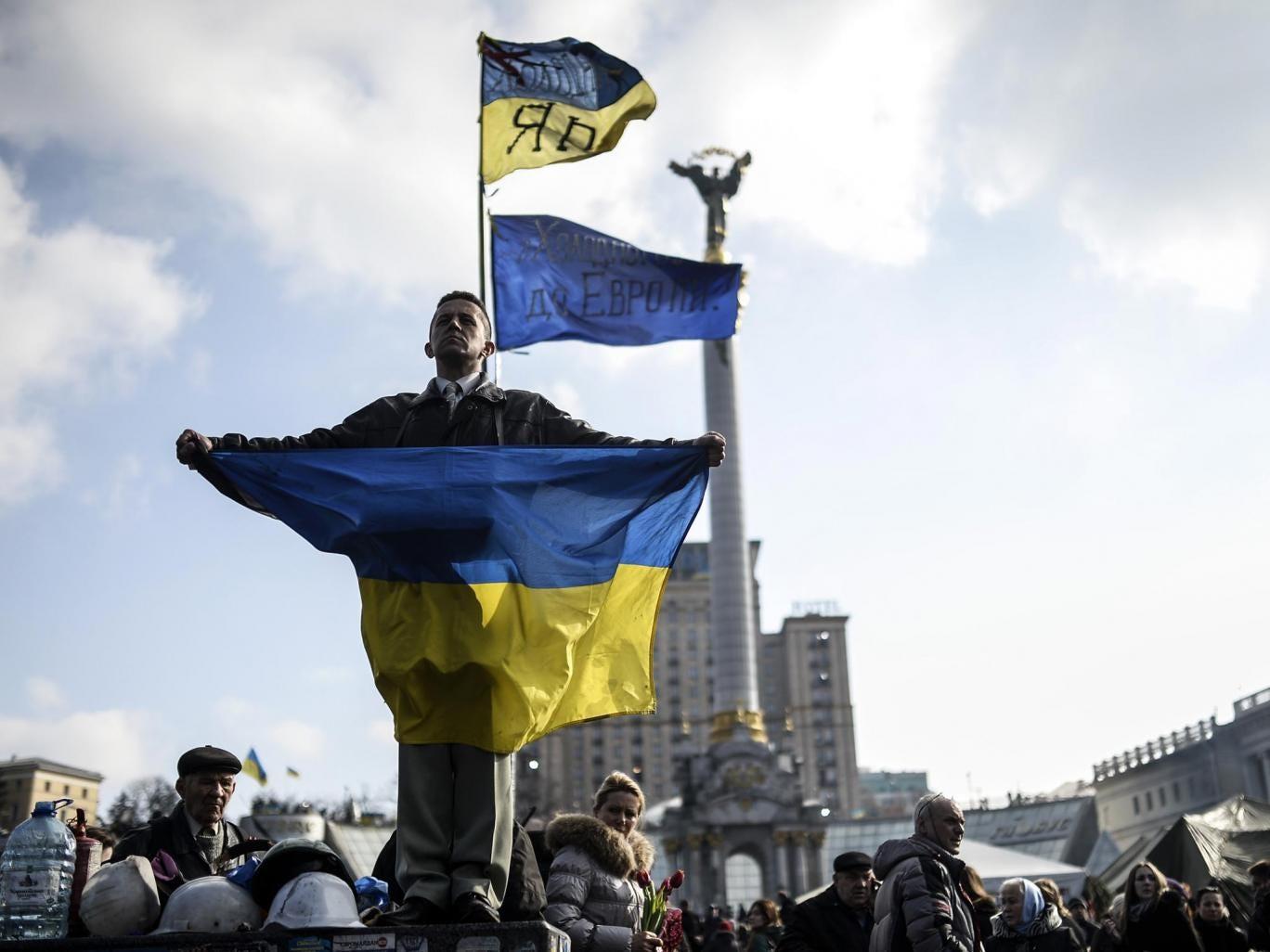 A protester wraps himself in the Ukraine flag in Kiev yesterday