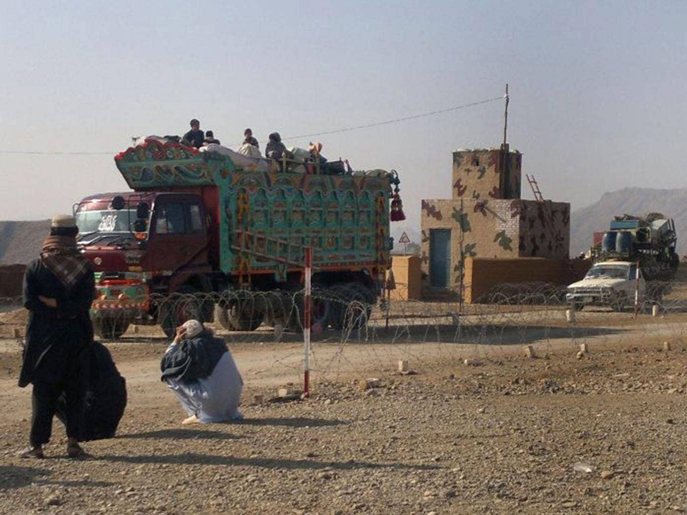 Pakistani tribal families cross a military check post as they flee after air strikes on Taliban hideouts