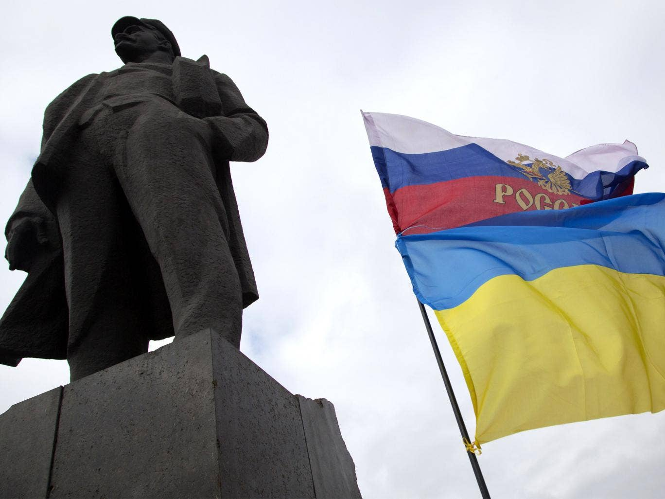 Russian and Ukrainian flags fly next to the statue of Vladimir Lenin, in Donetsk, eastern Ukraine
