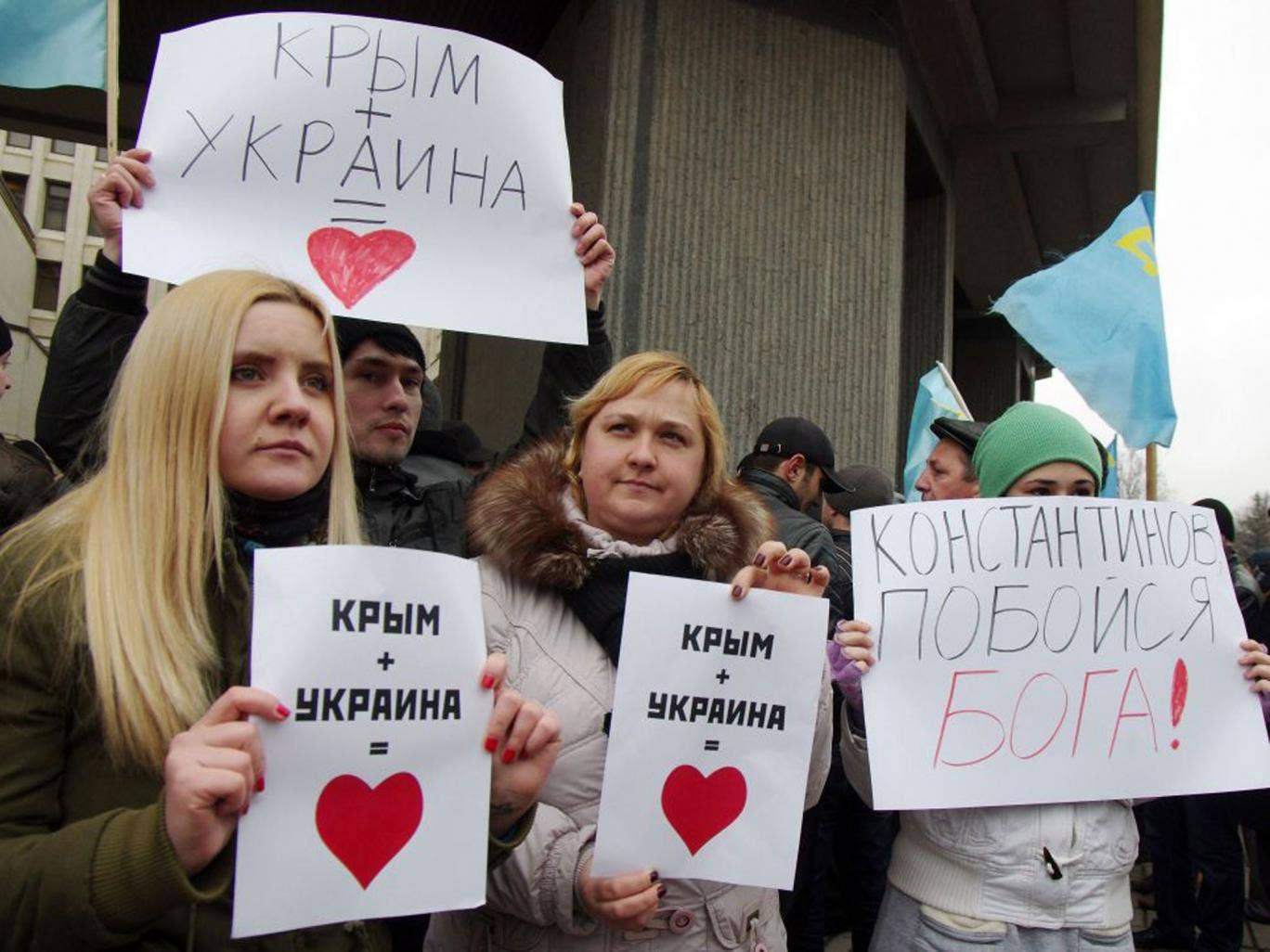 """Pro-Ukrainian activists hold placards reading """"Crimea+Ukraine is love"""" during a rally in front of the Crimean parliament in Semfiropol"""