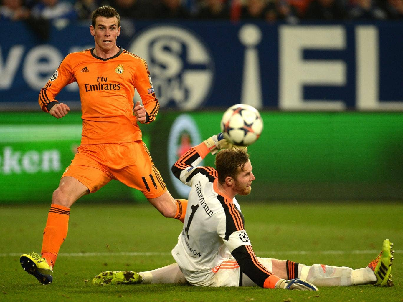 Real Madrid's Welsh striker Gareth Bale (L) scores against Schalke's goalkeeper Ralf Faehrmann during the first-leg round of 16 UEFA Champions League football match