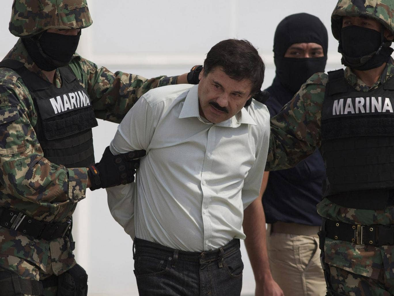 "Joaquin ""El Chapo"" Guzman is escorted to a helicopter in handcuffs by Mexican navy marines"