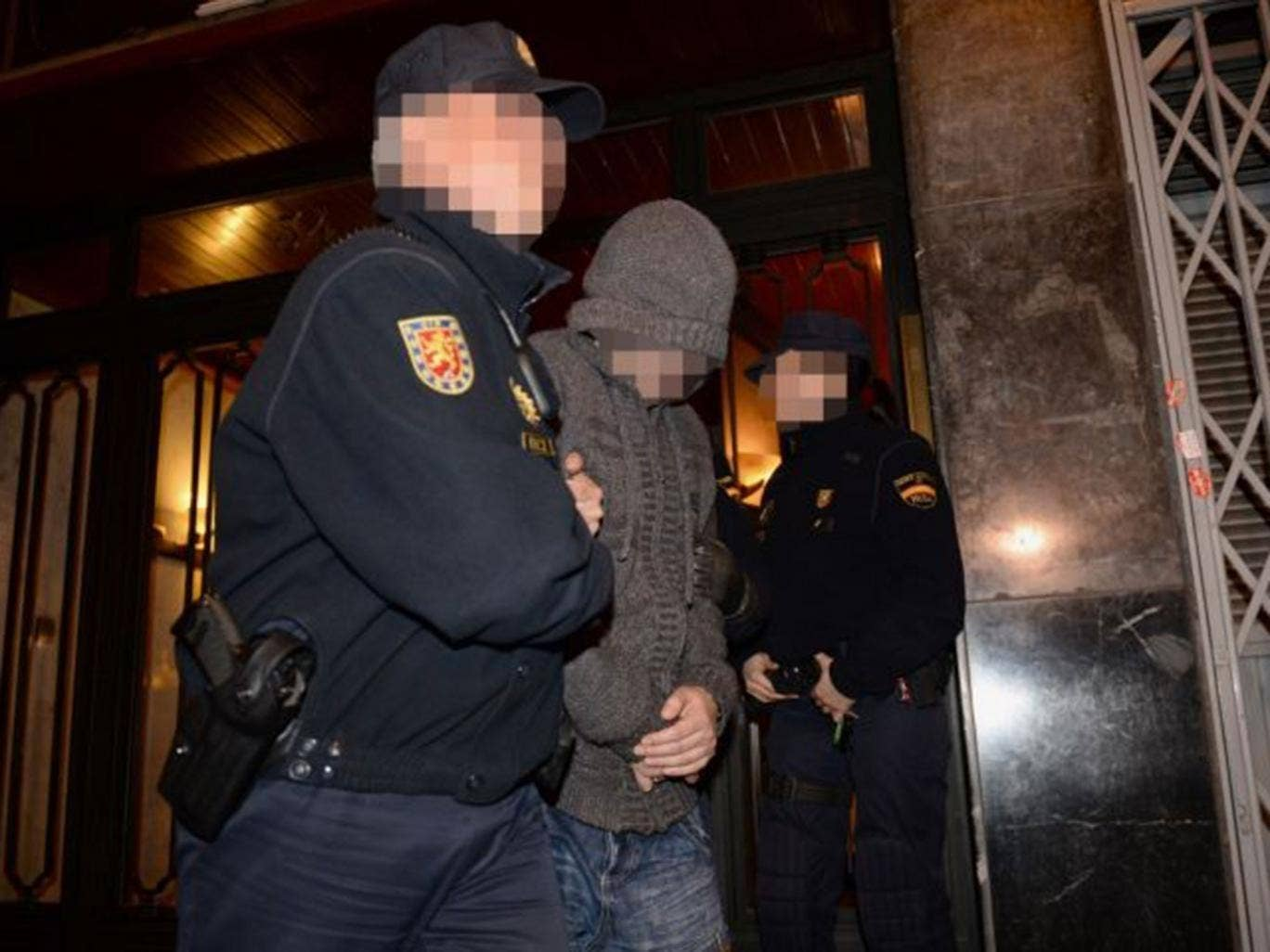 Officers from City of London Police and their Spanish counterparts from the Policia Nacional remove a suspect after raiding a business property in Barcelona