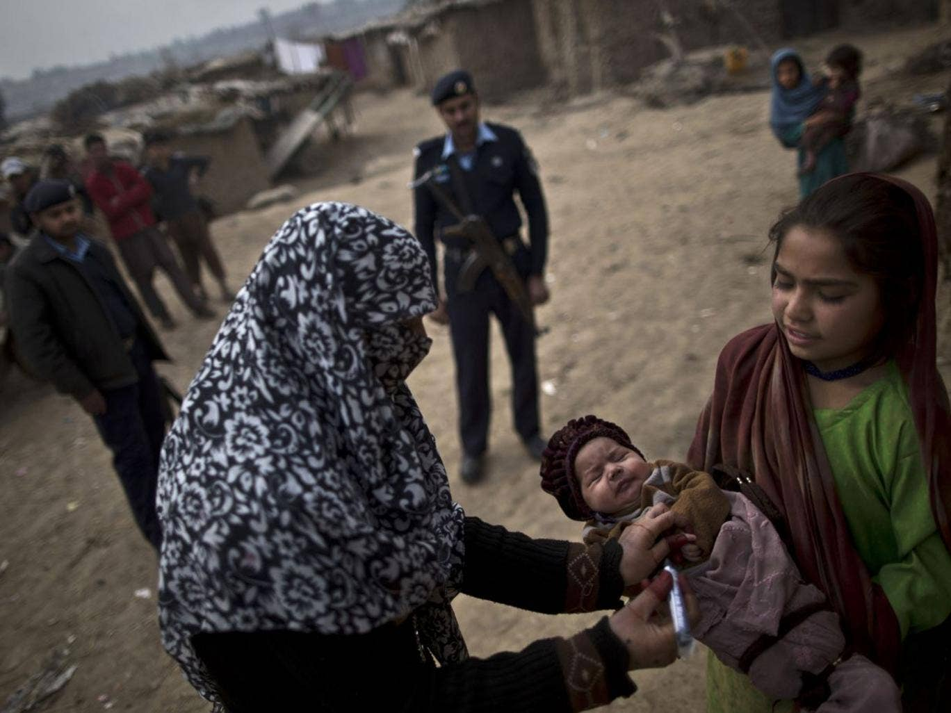 A Pakistani health worker marks the finger of an Afghan refugee child held by her elder sister, after giving her a polio vaccine, on the outskirts of Islamabad, Pakistan, on 26 February 2014