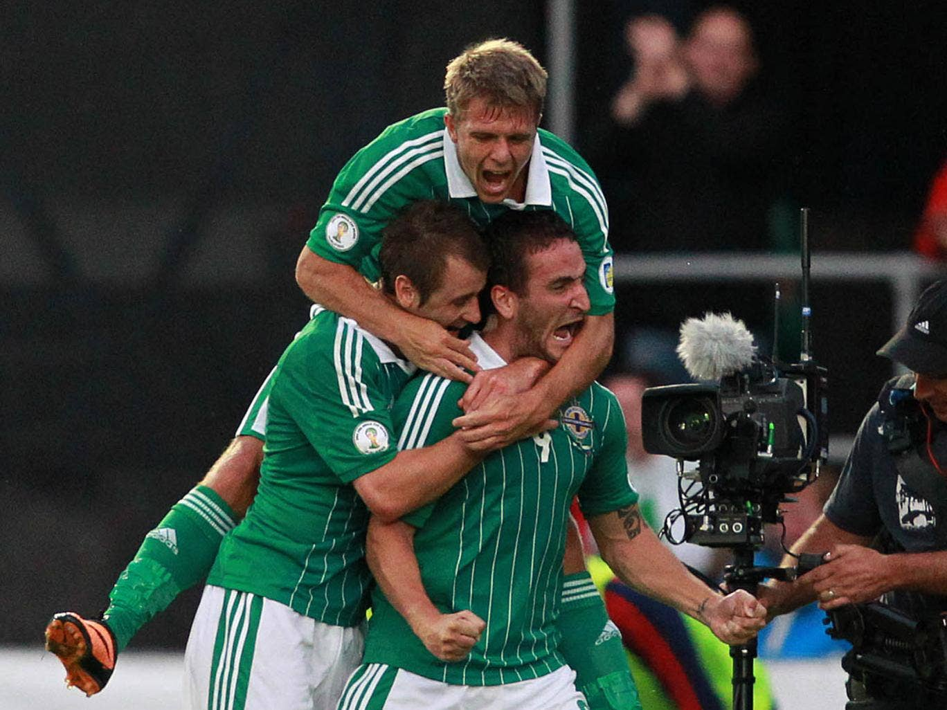 Northern Ireland's Martin Paterson (R) celebrates with team mates after scoring his team's first goal during the FIFA 2014 World Cup European zone group F qualifying football match between Russia and Northern Ireland