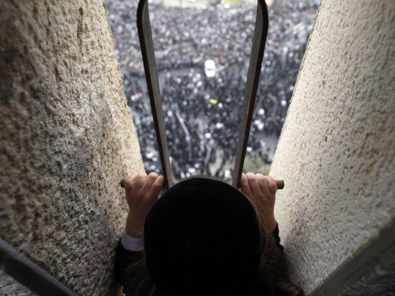 An ultra-Orthodox Jewish boy looks down from a balcony at a mass prayer in Jerusalem. Hundreds of thousands of ultra-Orthodox Jews held a mass prayer in Jerusalem on Sunday