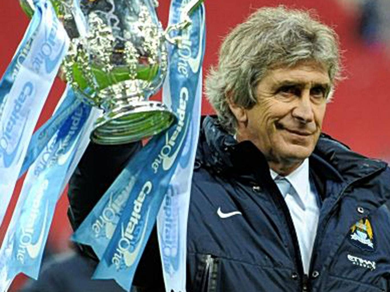 Manuel Pellegrini holds up the first major trophy he has won in Europe