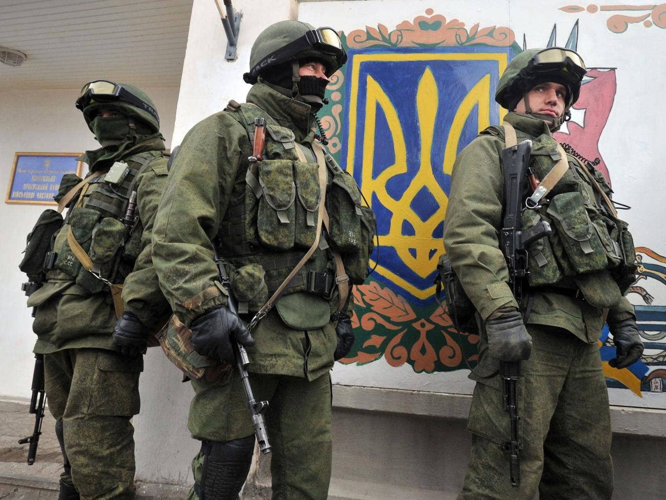 Armed men in military fatigues stand near a painted Ukrainian coat of arms symbol as they block access to a Ukrainian border guards base not far from the village of Perevalne near Simferopol