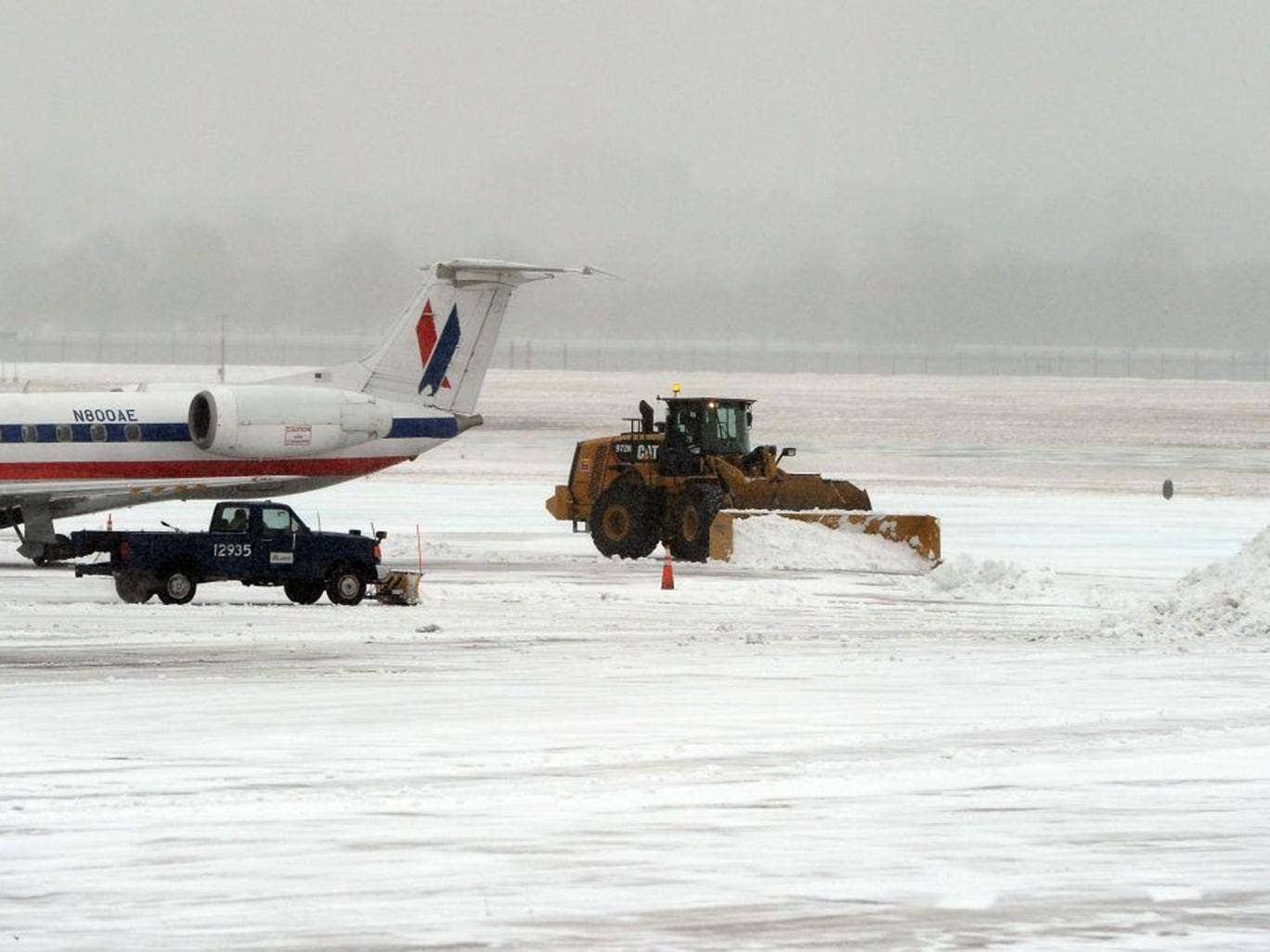 Workers use snowplows to clean a tarmac at the Reagan National Airport during a snow storm in Washington, DC