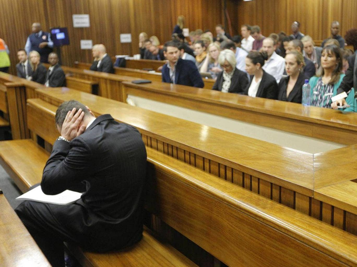 Oscar Pistorius blocks his ears inside the high court on the second day of his trial in Pretoria, South Africa
