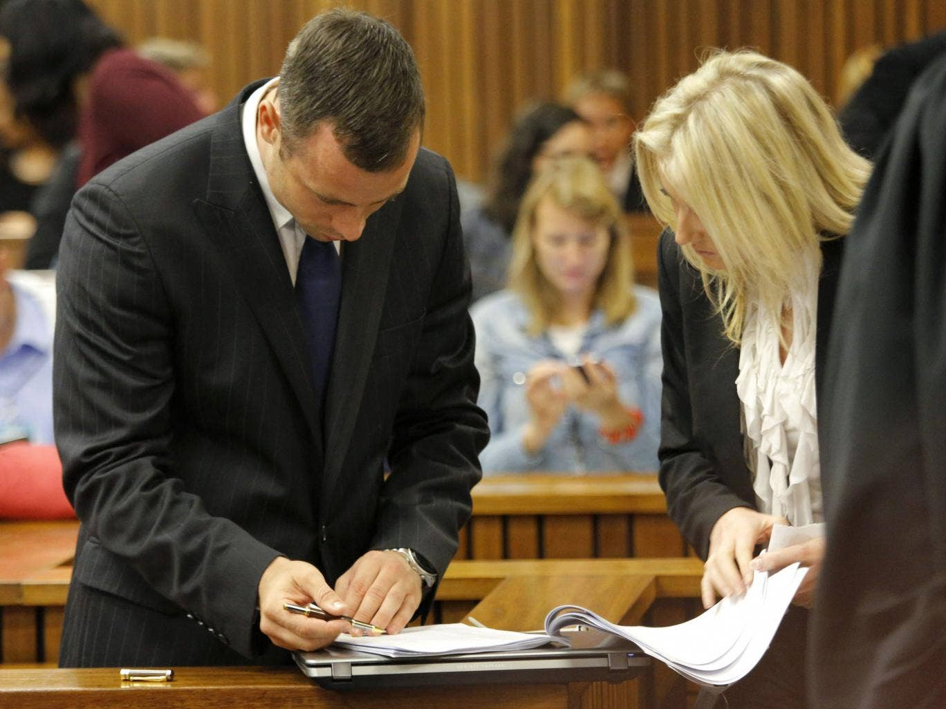 Oscar Pistorius looks at his defense team paperwork during a break on the second day of his trial at the North Gauteng High Court in Pretoria