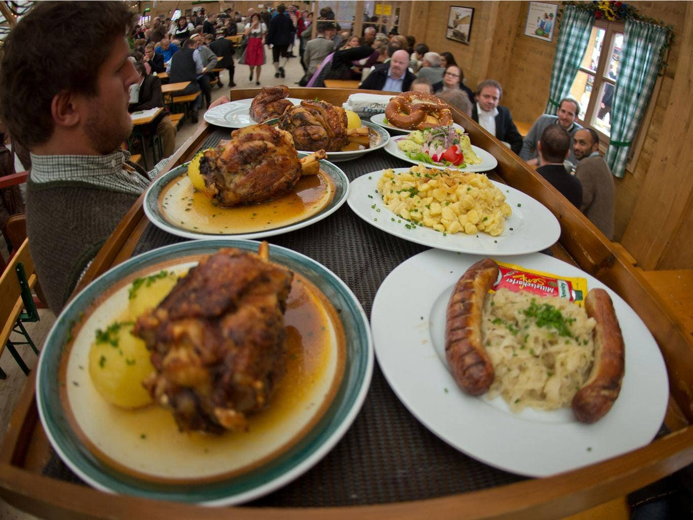 MUNICH, GERMANY - OCTOBER 1: A waiter carries a large tray of meals at the Oktoberfest 2013 beer festival at Theresienwiese on October 1, 2013 in Munich, Germany. This year some caterers offer vegetarian and vegan meals at the Oktoberfest. But as waiters