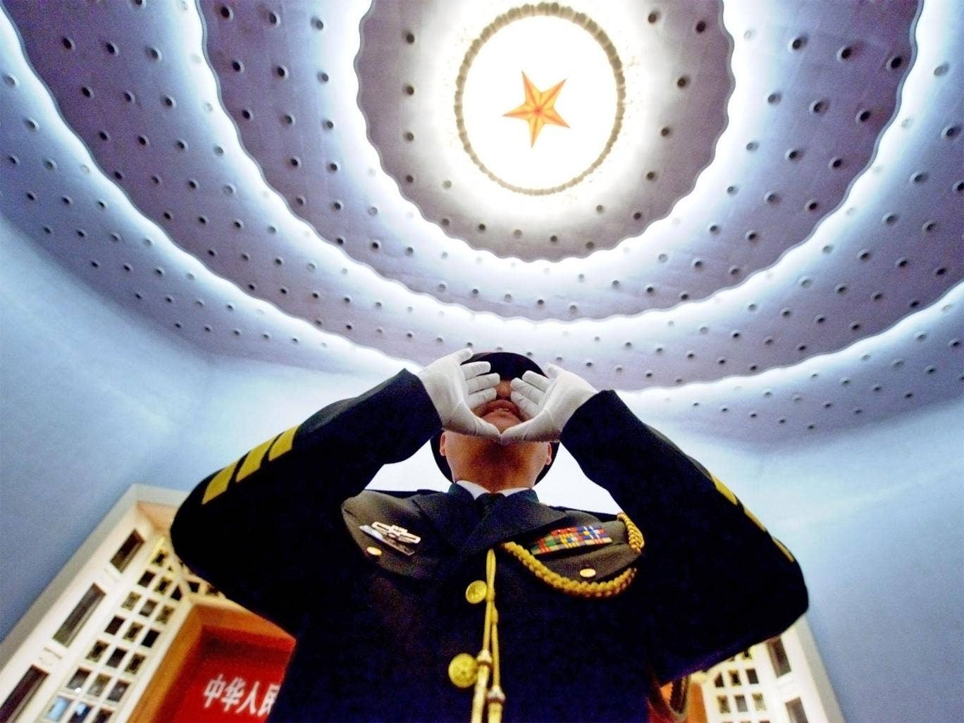 Top brass: an officer in the Chinese People's Liberation Army practises to conduct the military band before the opening session of the 12th National People's Congress in Beijing