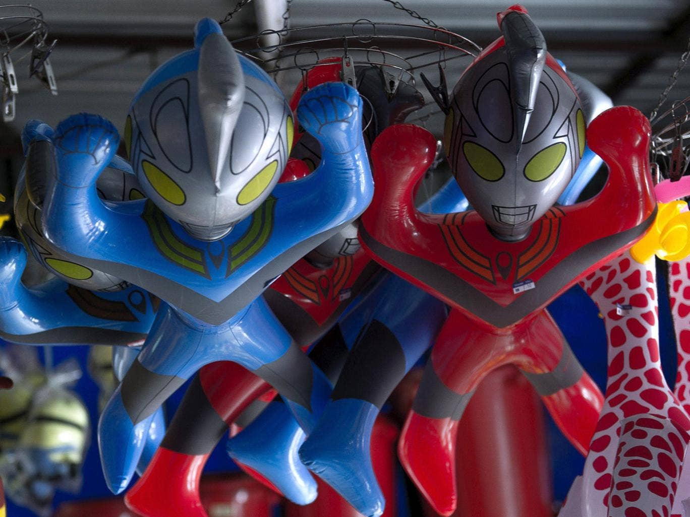 Plastic toys of the popular Japanese superhero Ultraman hang from the ceiling of a shop in Malaysia