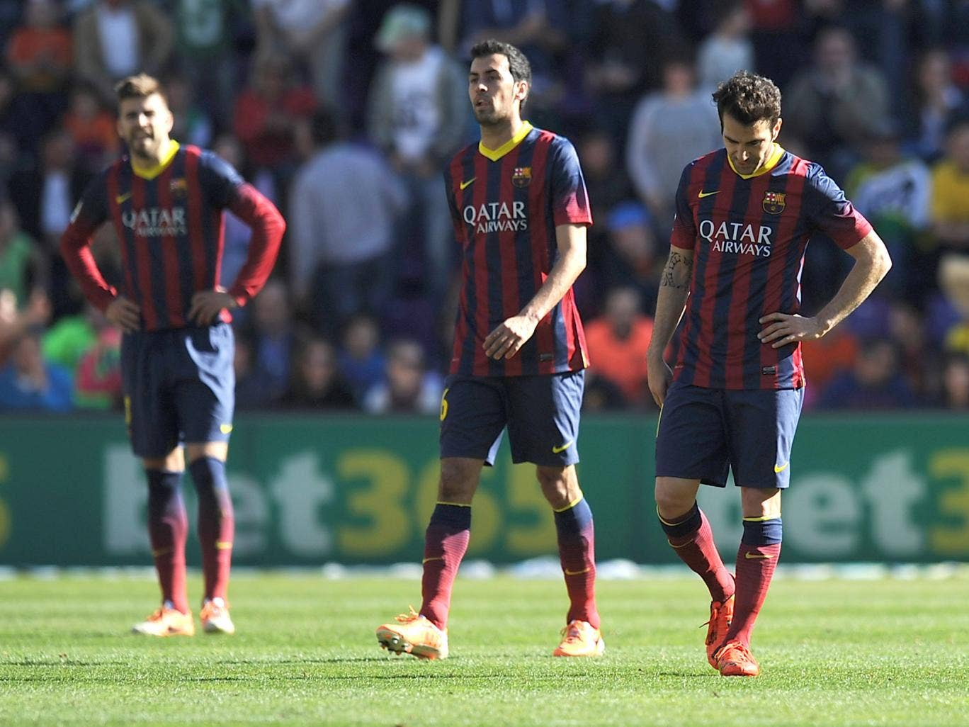 Gerard Pique, Sergio Busquets and Cesc Fabregas react to Barcelona's defeat against Valladolid
