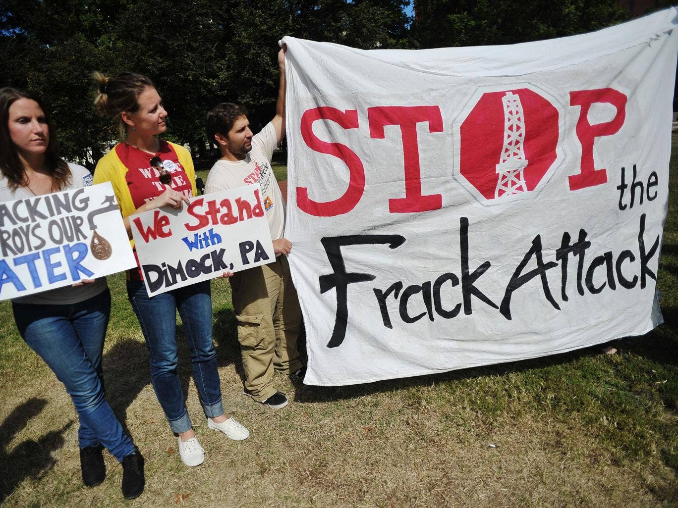 Opponents of hydraulic fracturing or 'fracking' hold placards during a rally in Lafayette Square, across from the White House in DC