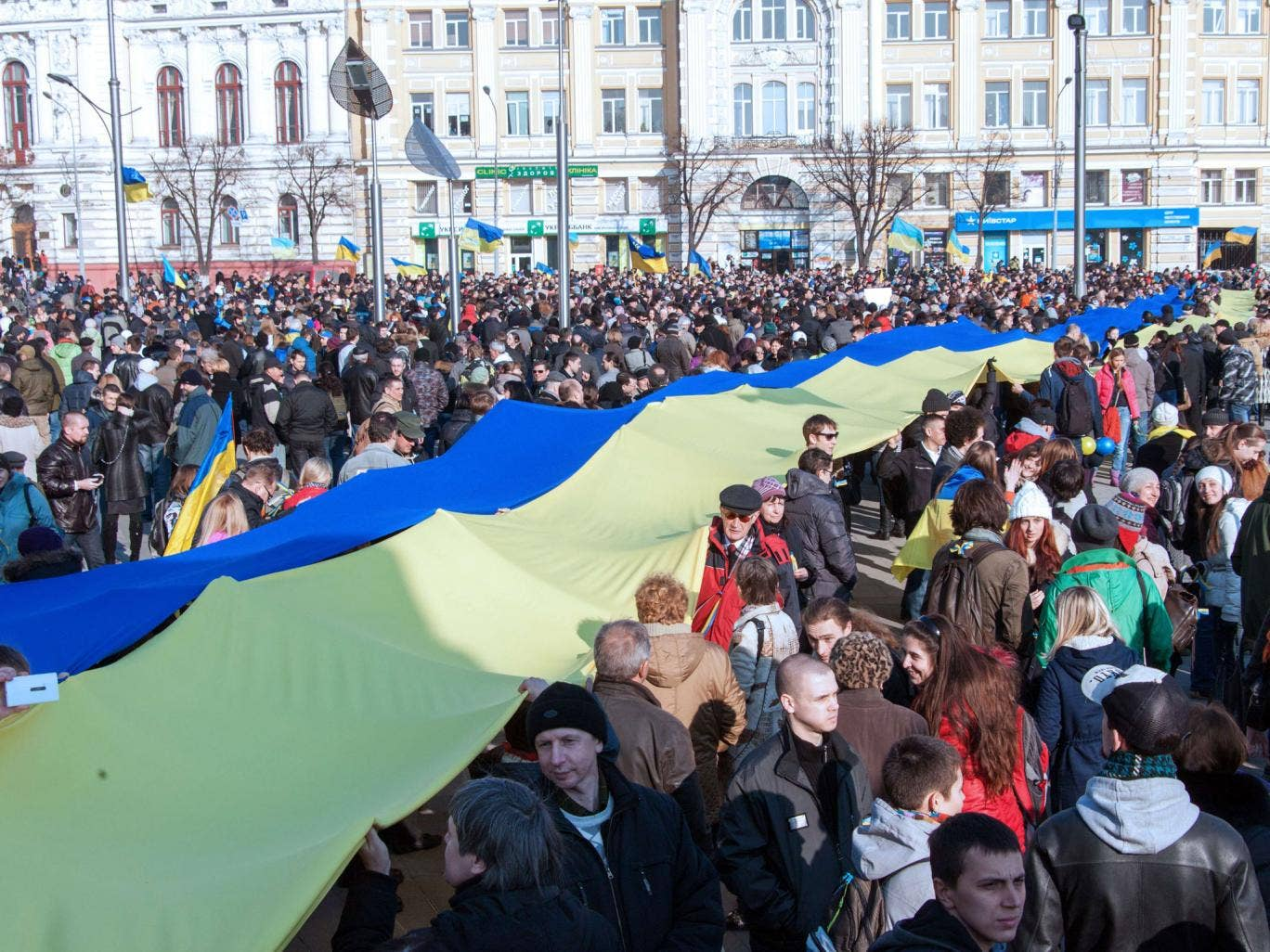 Protesters carry a giant Ukrainian flag during yesterday's anti-war rally in Kharkiv, north-eastern Ukraine, as the world's leaders seek a solution to the stand-off