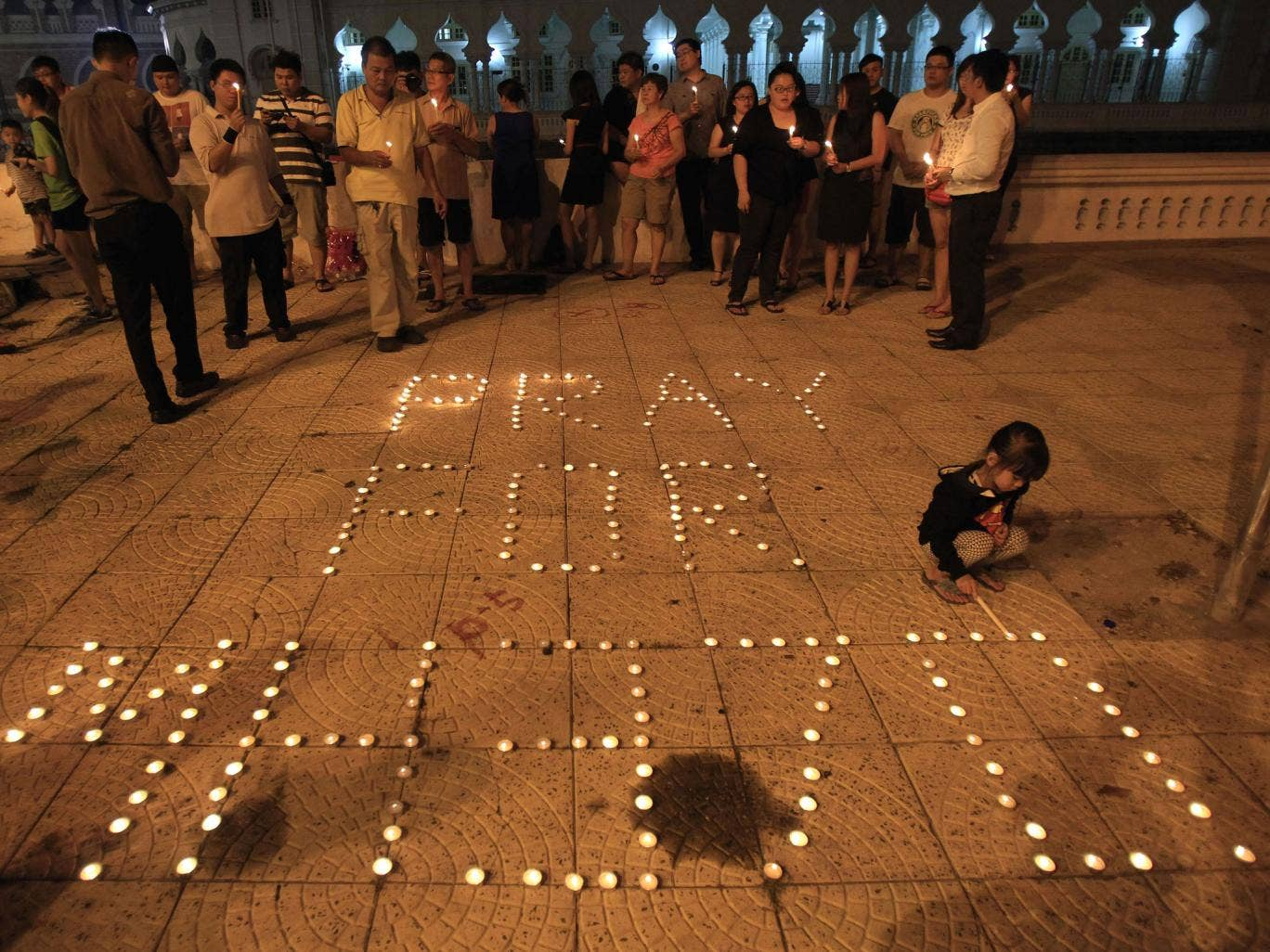 A girl lights a candle next to a message reading 'Pray for MH370' during a candlelight vigil for passengers of the Malaysia Airlines flight