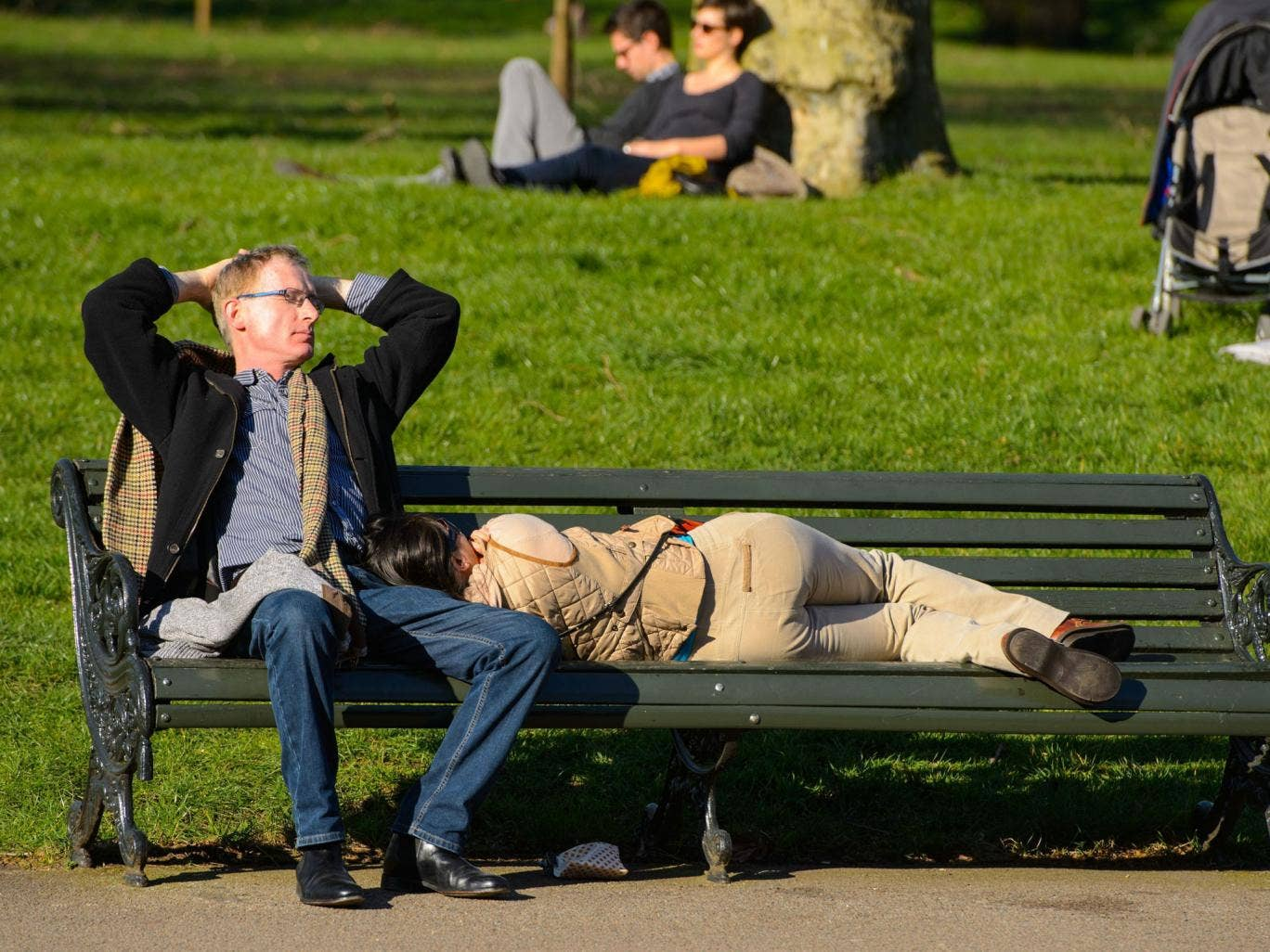 People sleep in the sun on a bench as they enjoy the weather in Hyde Park, central London