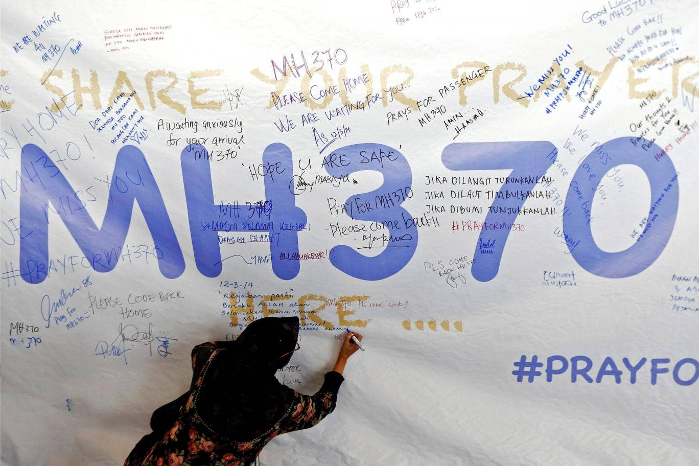 A woman writes a message of support and hope for the passengers of the missing Malaysia Airlines MH370 on a banner at Kuala Lumpur International Airport