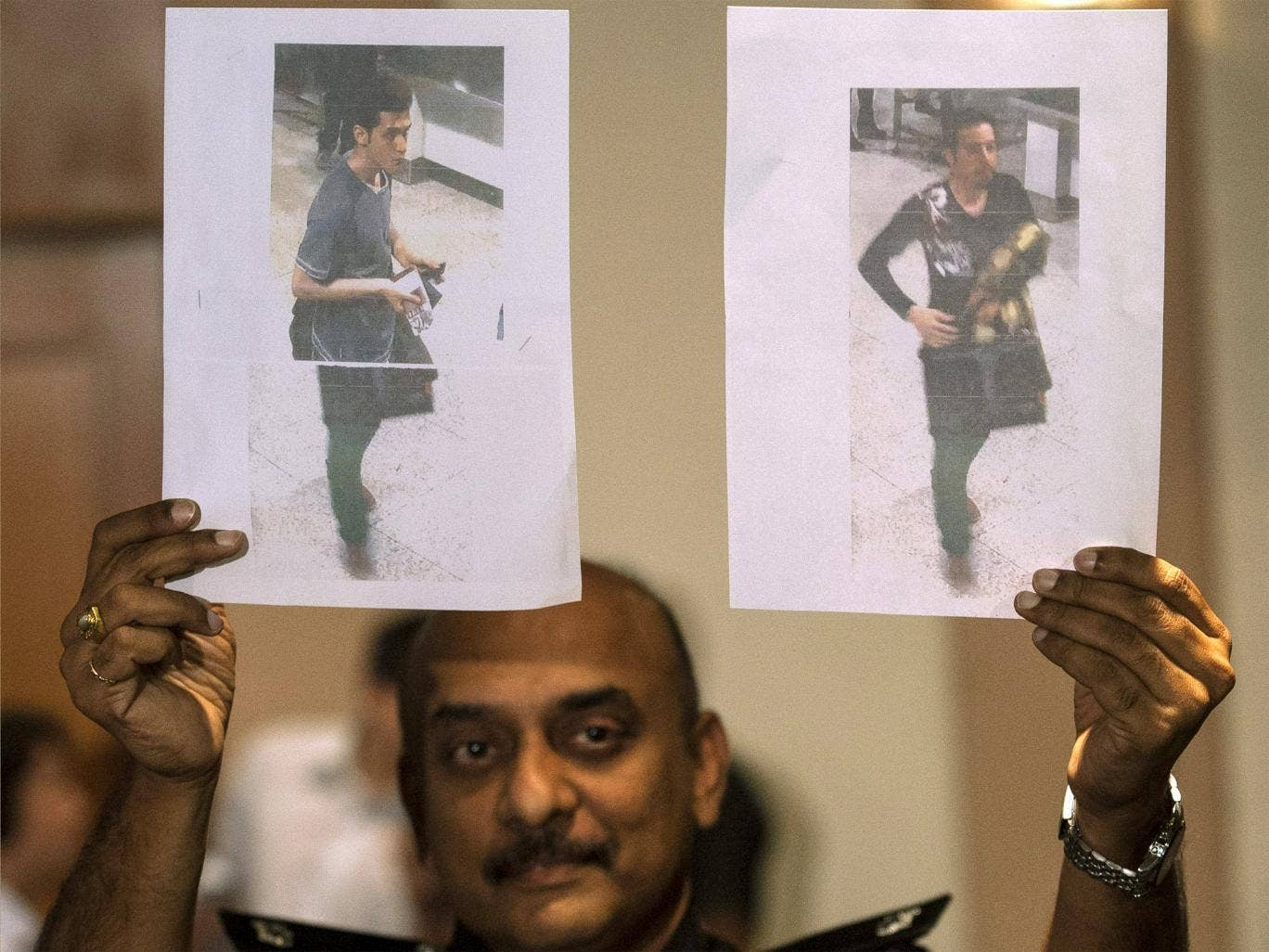A Malaysian Police officer holds photos of two suspects believed to have travelled with stolen passports on the missing Malaysian Airlines flight