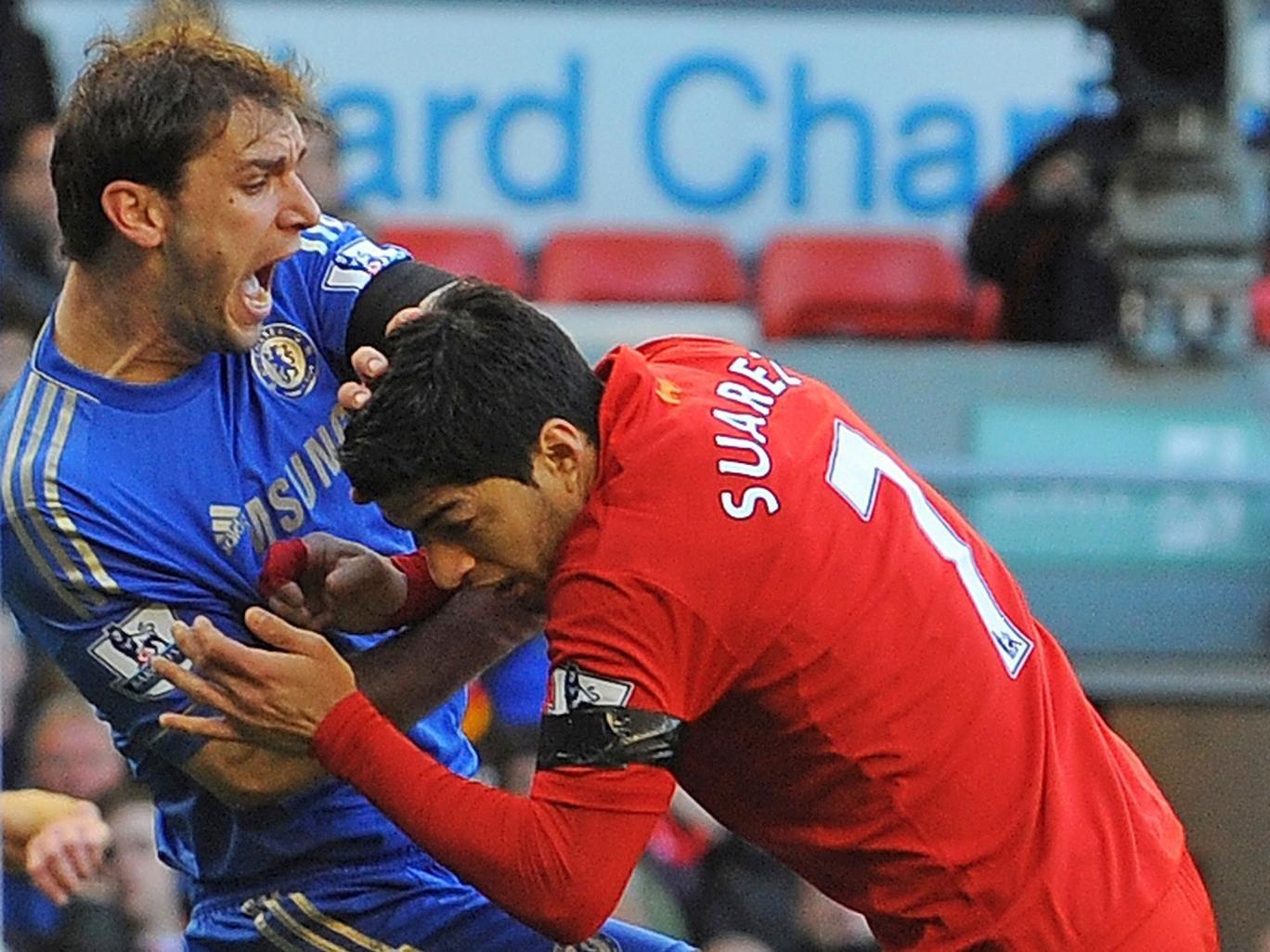 Uruguayan striker Luis Suarez (R) clashes with Chelsea's Serbian defender Branislav Ivanovic (L)