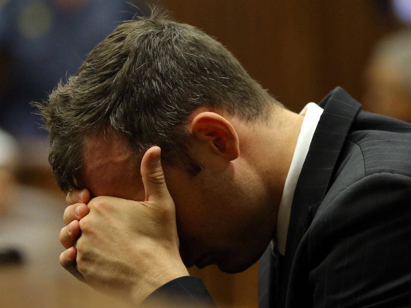 Oscar Pistorius places his head in his hands as he listens to the cross examination during his trial in court in Pretoria