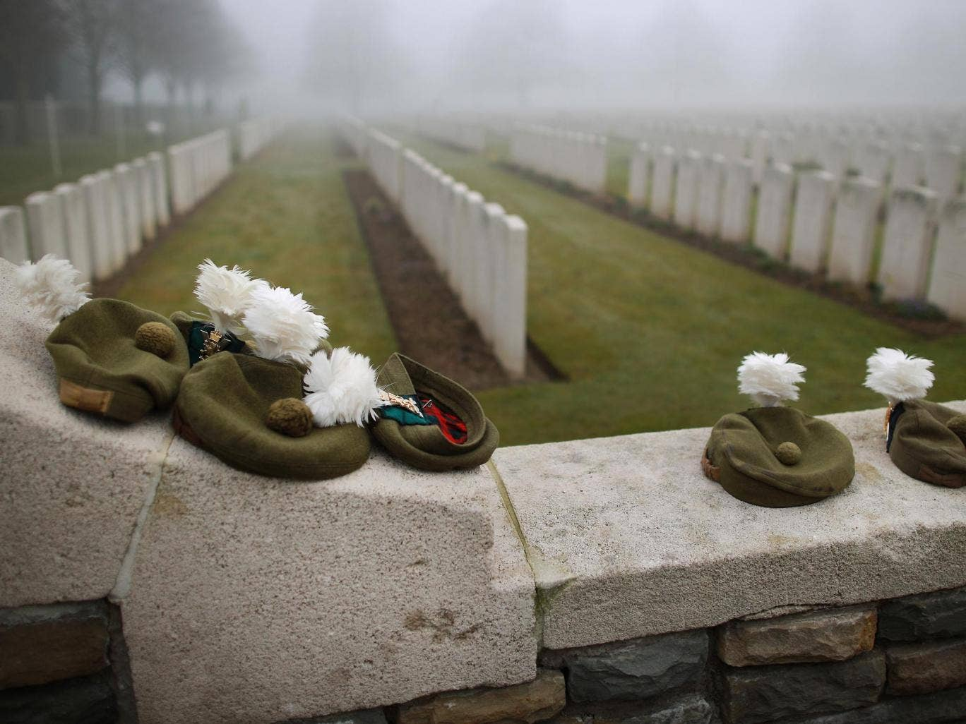 Military Tam O Shanter caps belonging to soldiers of The 2nd Battalion The Royal Regiment of Scotland are placed on the wall of  Loos British Cemetery