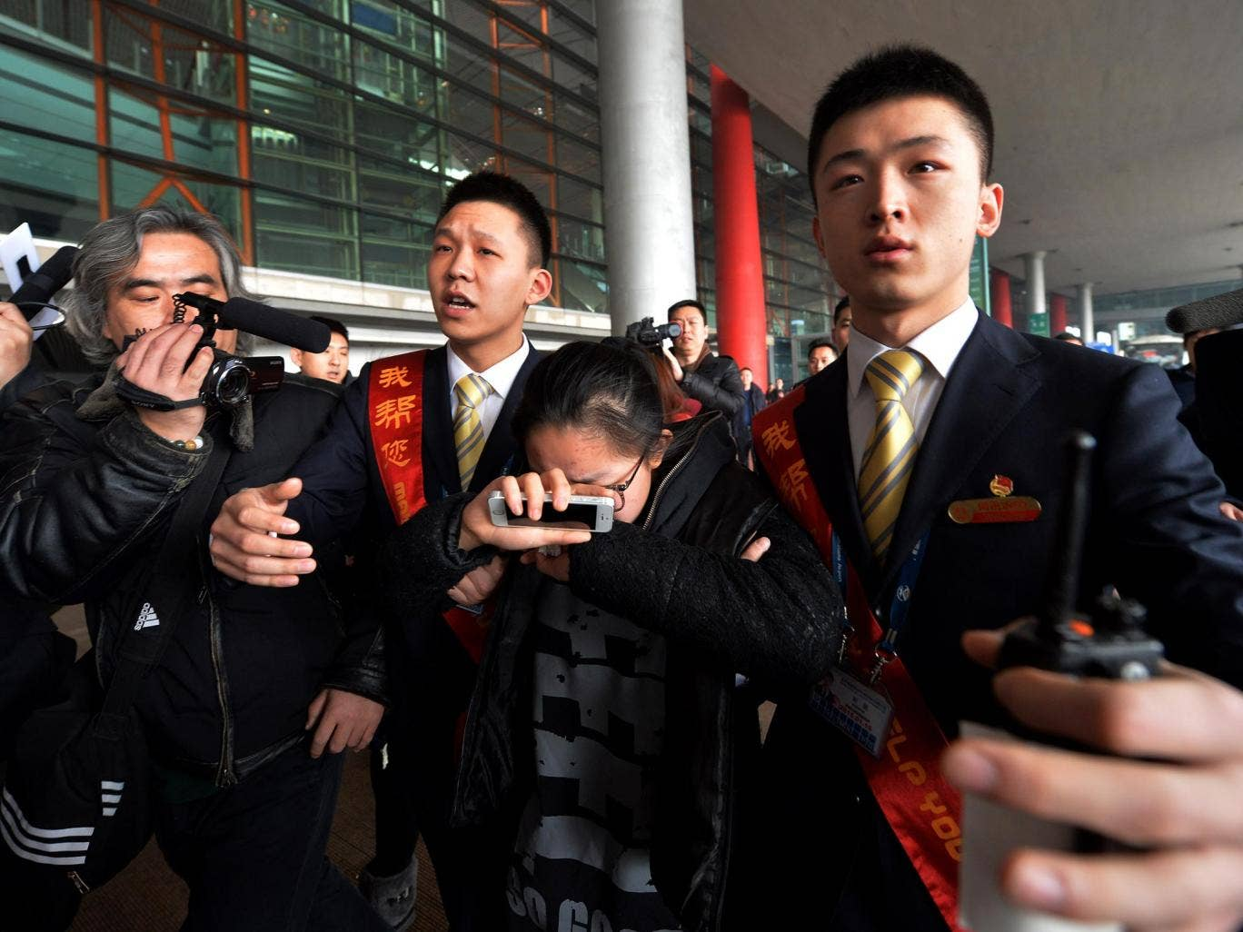 A crying woman is escorted to a bus for relatives at the Beijing Airport after news of the missing Malaysia Airlines Boeing 777-200 plane