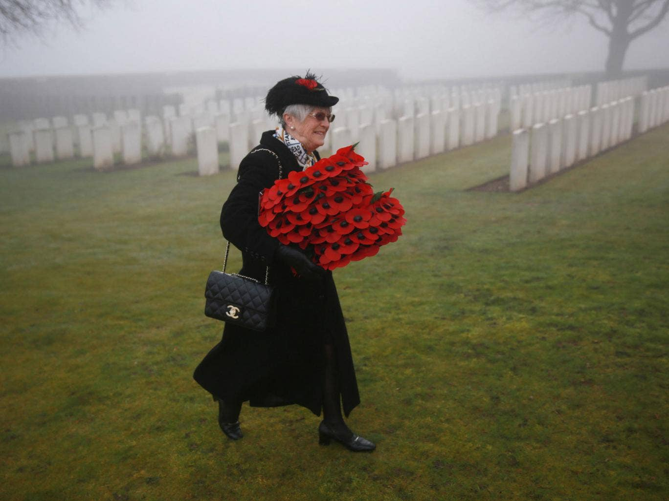 A mourner carries wreaths before the re-burial of Private William McAleer at Loos British Cemetery in Loos-en-Gohelle