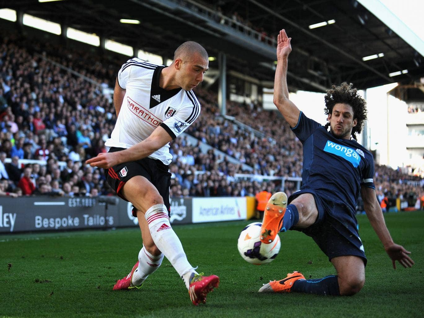 Pajtim Kasami of Fulham tackled by Fabricio Coloccini of Newcastle United