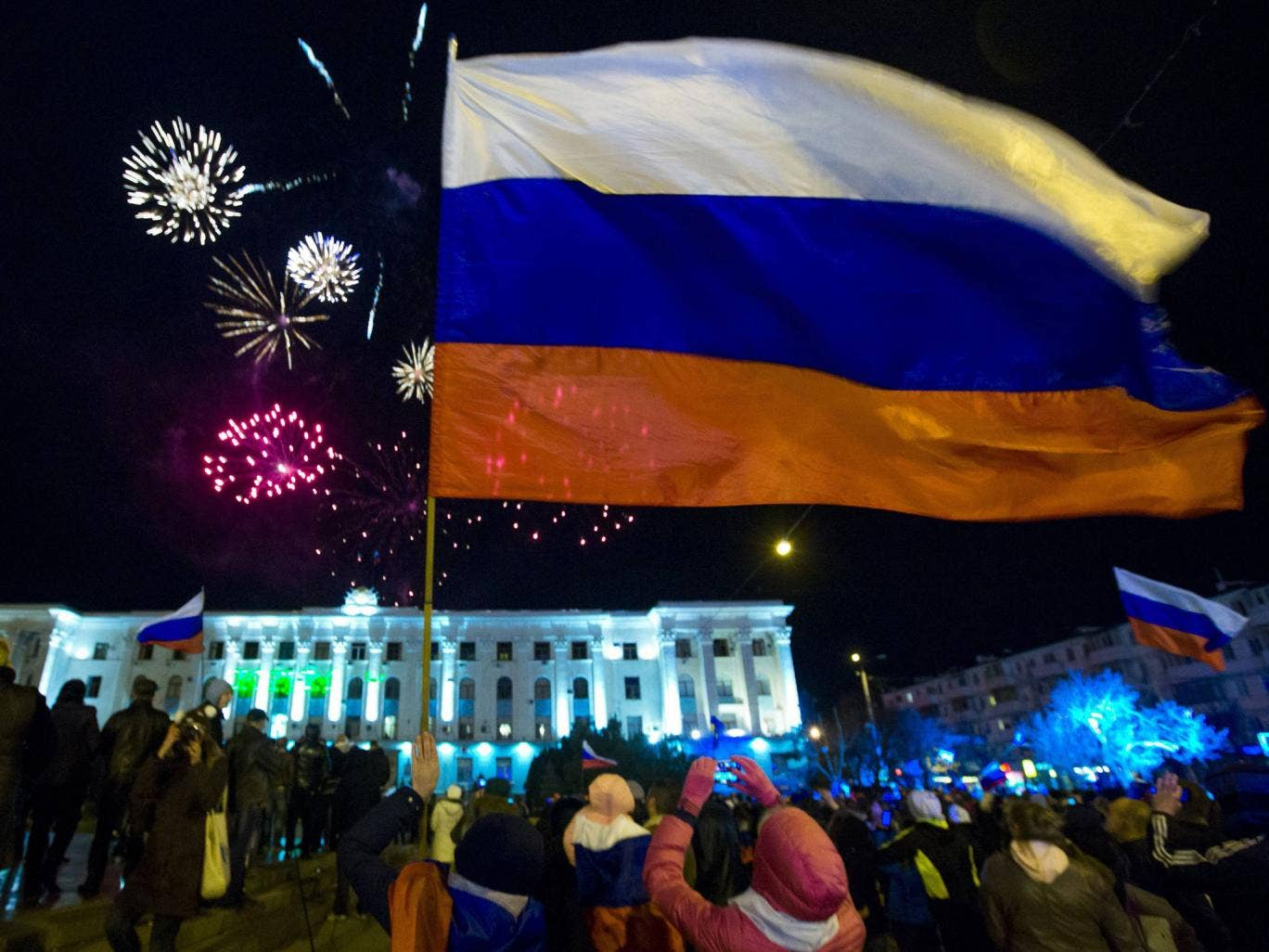 People watch fireworks and wave Russian flags during celebrations after the preliminary results of today's referendum are announced on Lenin Square in the Crimean capital of Simferopol