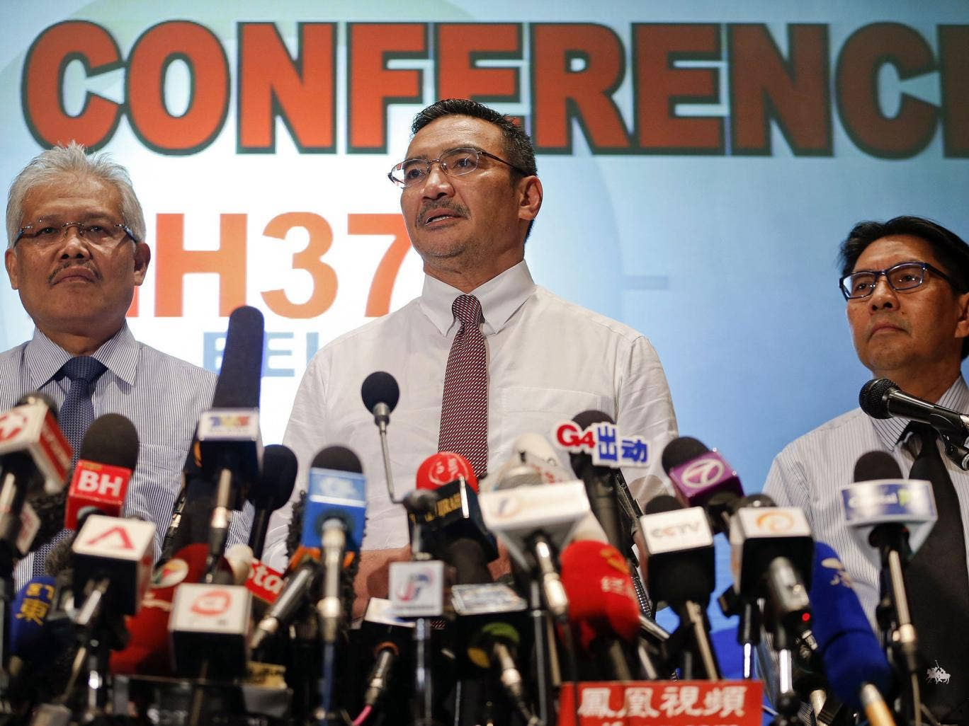 Malaysia's acting Transport Minister Hishammuddin Hussein (C) is accompanied by Deputy Foreign Minister Hamzah Zainudin (L) and Department of Civil Aviation's Director General Azharuddin Abdul Rahman as he addresses reporters about the missing Malaysia Ai