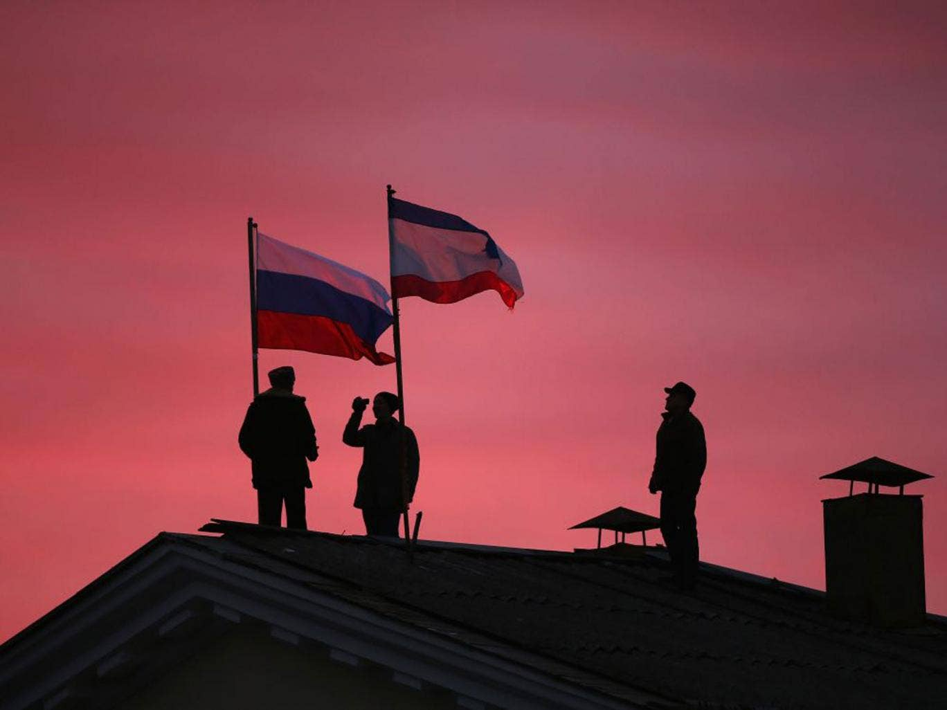 Cossack men install a Russian and a Crimean flag on the roof of the City Hall building