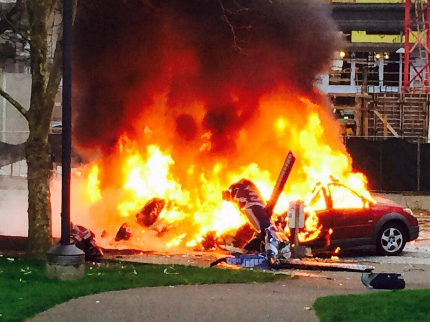 A car burns at the scene of a helicopter crash outside the KOMO-TV studios near the space needle in Seattle
