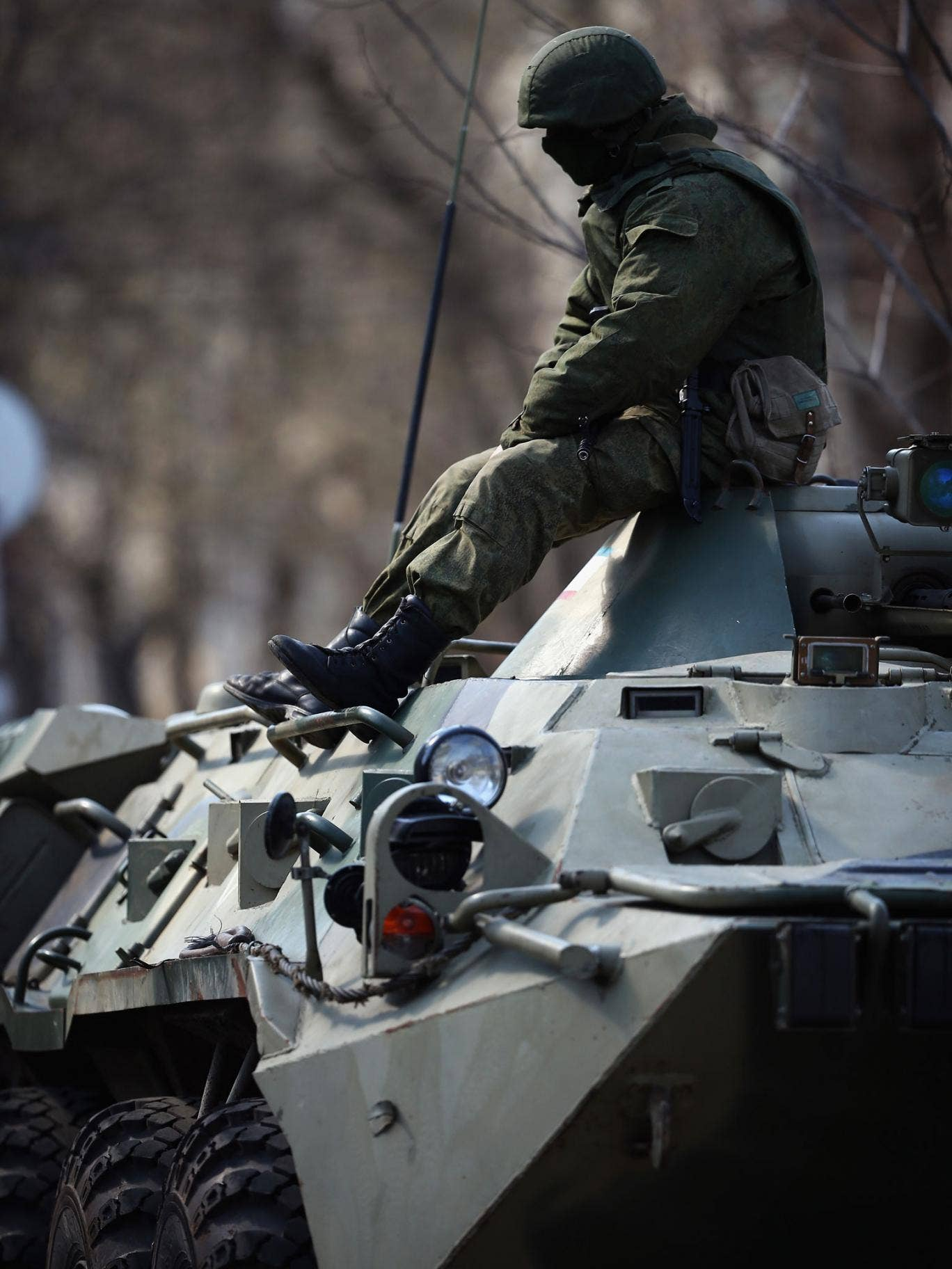A Russian military man sits on top of a Russian military personnel carrier outside a Ukrainian military base on March 18, 2014 in Simferopol, Ukraine