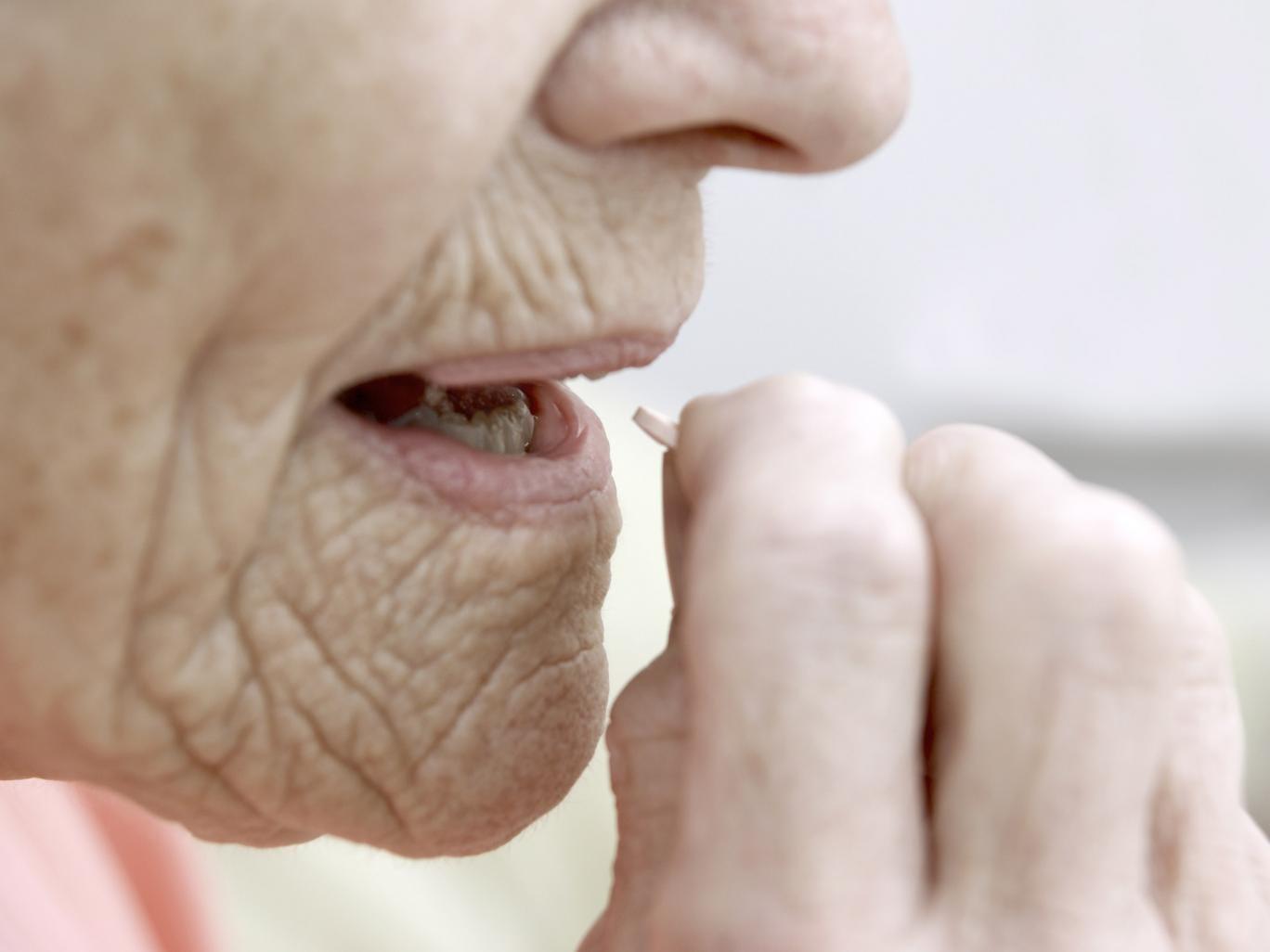 An elderly woman takes statin medication